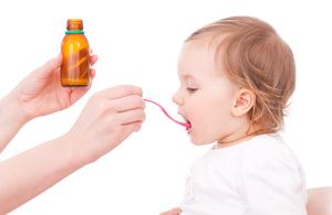 bébé enfant prend un médicament sirop cuillère
